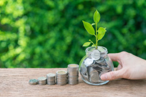 Hand holding jar with full of coins with growth sprout plant as financial investment concept.
